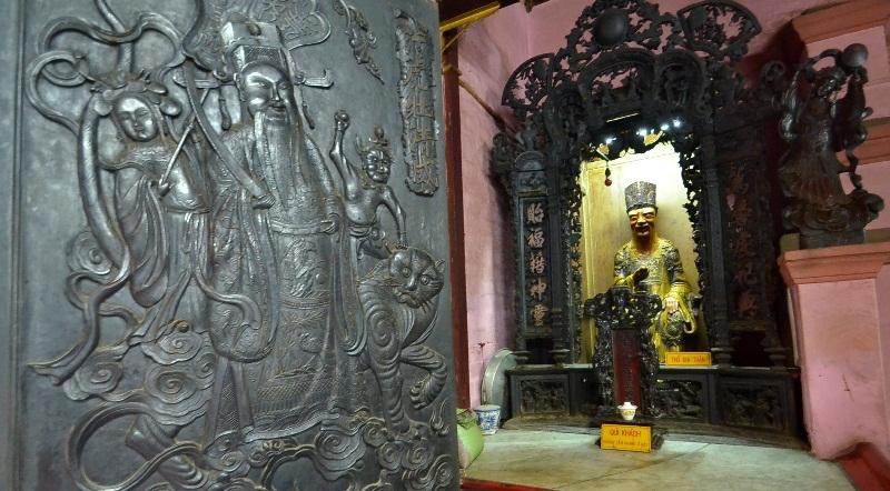 Bàn thờ thổ địa bên trái lối vào và cánh cửa chính chạm trổ khá công phu.